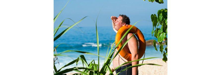 Schwitzender Mann mit Rettungsring hält Ausschau am Strand