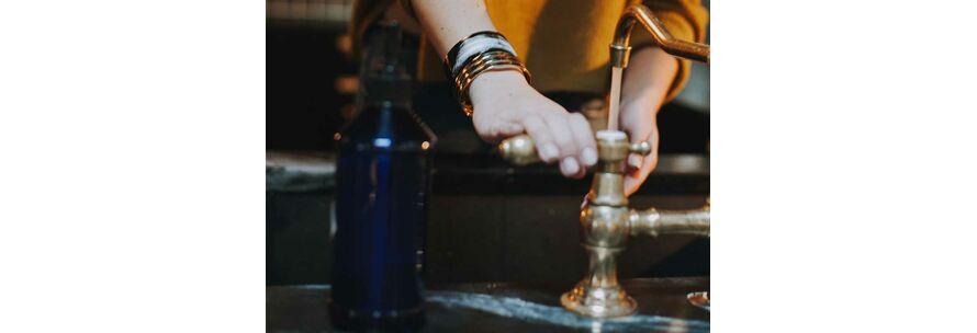 junge Frau wäscht Hände unter historischer Armatur